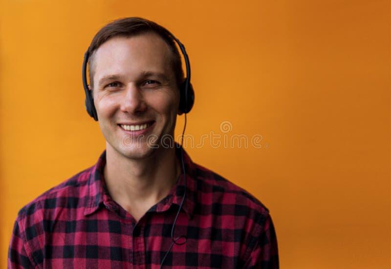 年轻愉快的帅哥佩带的耳机和享受在黄色背景的音乐 免版税库存图片