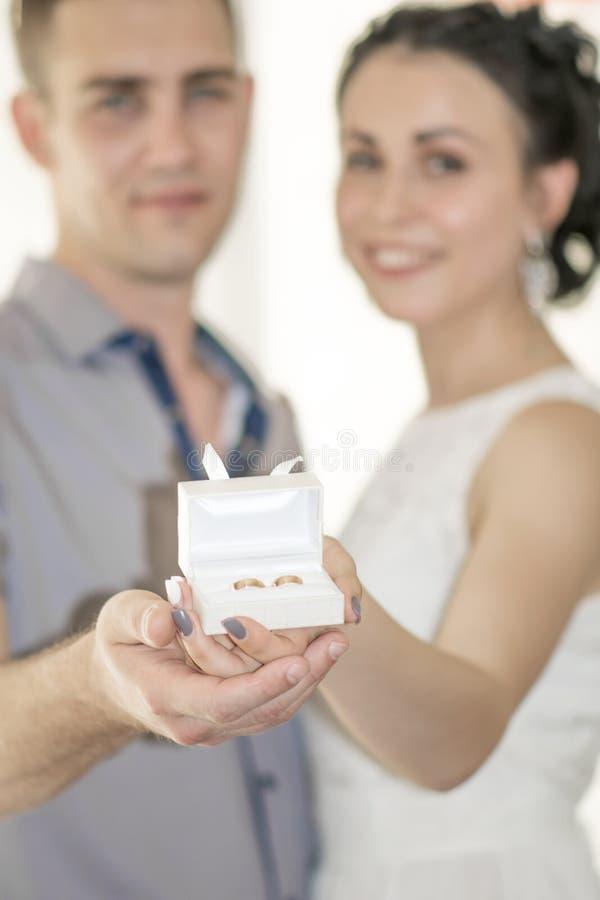 年轻愉快的微笑的拿着婚礼或定婚戒指在小白色礼物盒的coulpe新娘和新郎Defocused画象  免版税图库摄影