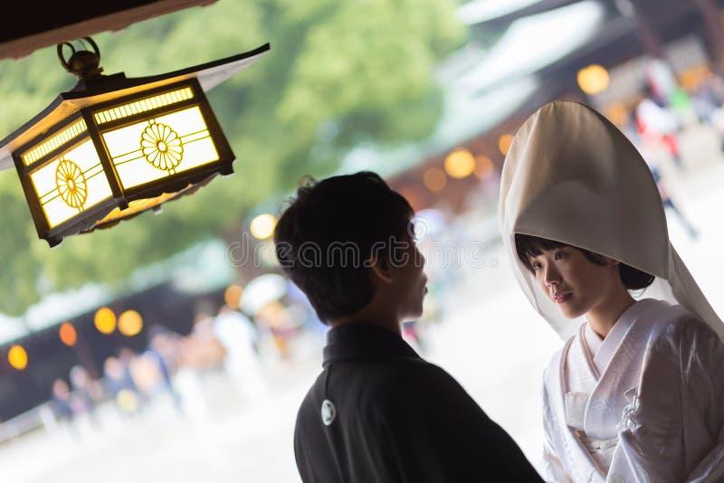 年轻愉快的新郎和新娘在日本传统婚礼期间在美济礁神功皇后寺庙在东京,日本  免版税库存图片