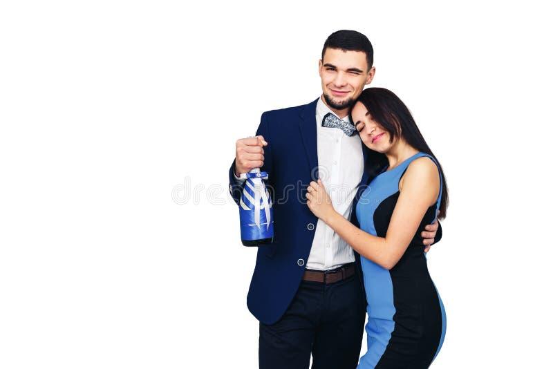 年轻愉快的时髦的加上在蓝色衣服和一个装饰的瓶香槟或酒 免版税库存图片