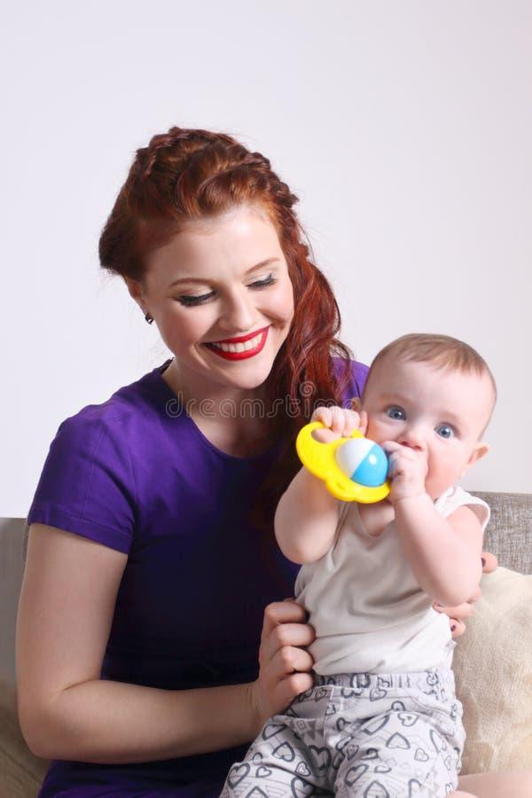 年轻愉快的母亲坐与她的有玩具的小婴孩 免版税库存照片
