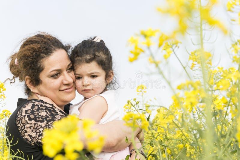 年轻愉快的母亲拥抱了她哀伤的女孩在油菜领域 免版税库存图片