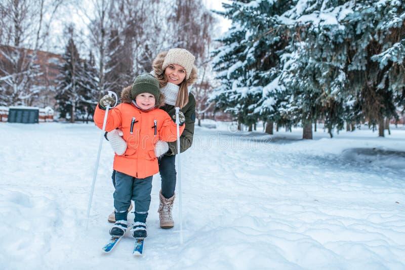 年轻愉快的母亲,妇女拿着一个男孩2-5岁儿子,学会滑雪 在冬天在外面公园 照料婴孩 免版税图库摄影