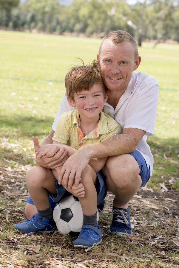 年轻愉快的父亲和激动的7或8岁一起踢在城市公园庭院的儿子足球橄榄球摆在甜和爱的h 库存图片