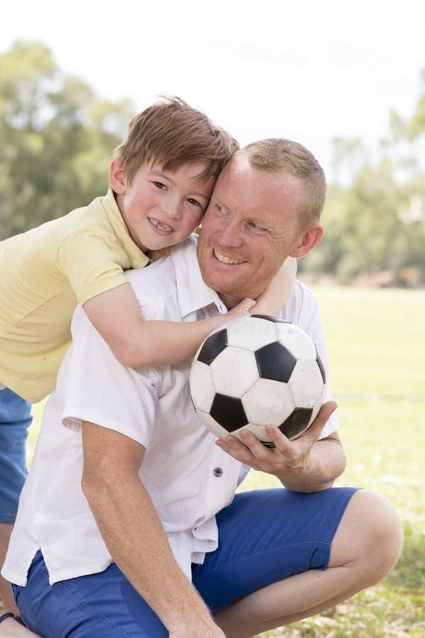 年轻愉快的父亲和激动的7或8岁一起踢在城市公园庭院的儿子足球橄榄球摆在甜和爱的h 免版税库存图片