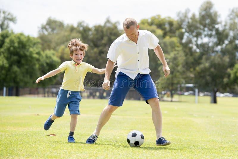 年轻愉快的父亲和激发一点7或8岁一起踢在城市公园庭院的儿子足球橄榄球跑在草k 免版税库存图片