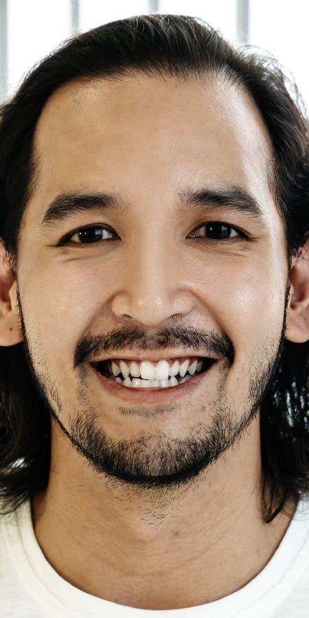年轻愉快的短的时髦的有胡子的亚裔人或创造性的设计师微笑和看感到的照相机画象确信 免版税库存照片
