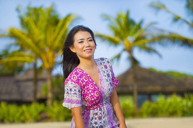 年轻愉快的美丽的亚裔中国旅游走在海滩热带手段的妇女微笑的放松的佩带的甜礼服在度假 免版税库存图片