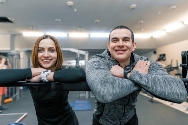 年轻愉快的运动的夫妇画象,男人和妇女微笑的调查照相机,健身房背景 库存照片