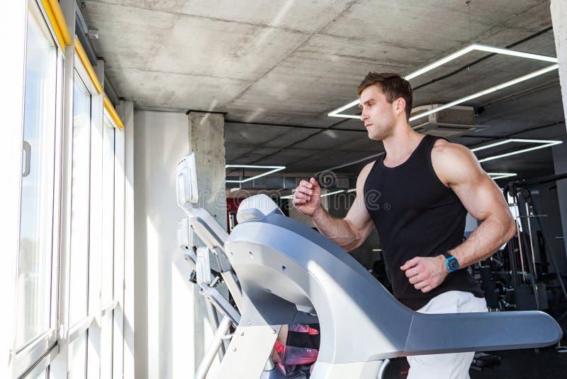 年轻成人人侧视图画象运行在踏车的运动服的在健身房 英俊的在踏车的阳刚之气男性训练 库存照片