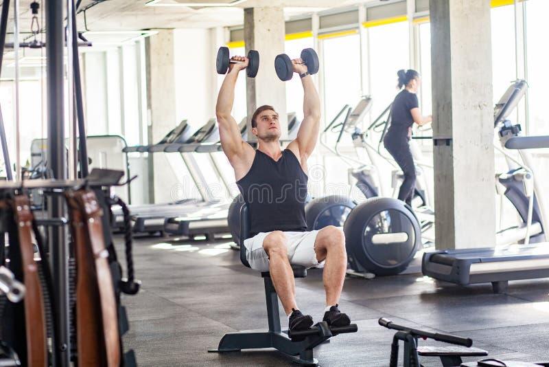 年轻成人体育人训练画象在单独健身房的 解决在健身房,坐和举行两哑铃与的运动员 免版税库存图片