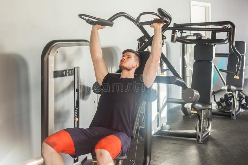 年轻成人体育运动员人训练画象在健身房和单独举的重量的,当坐在健身房时的长凳 库存照片