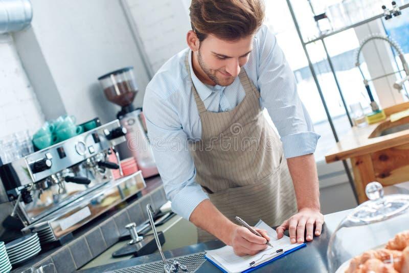 年轻成人咖啡师在餐厅工作记录 免版税库存图片