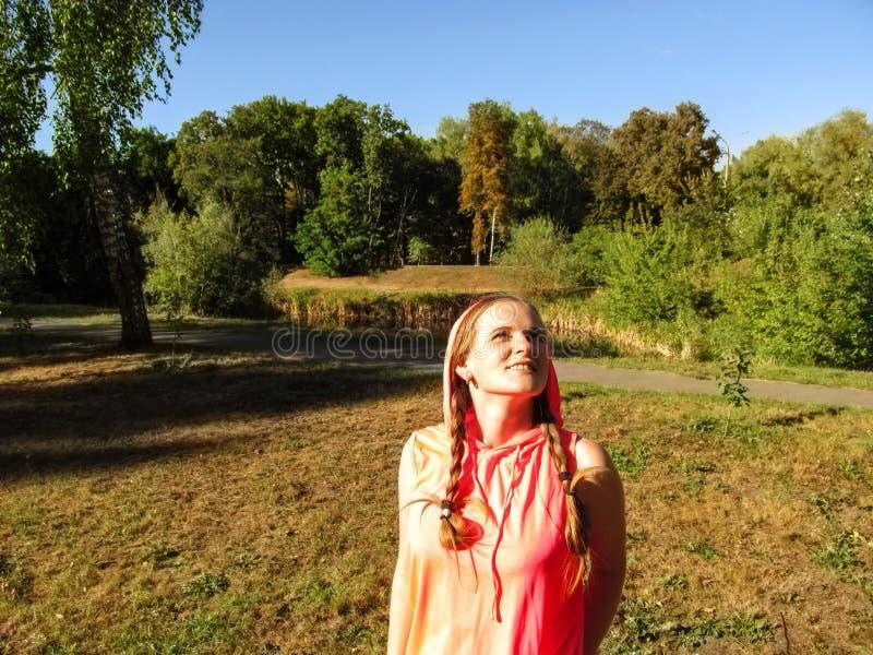 年轻成人女孩画象有两条猪尾佩带的戴头巾,微笑,看天空在公园 愉快享用的概念 库存照片