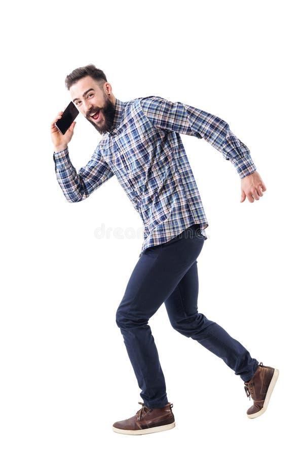 年轻成人有胡子的商人跑和谈话在手机 免版税库存图片