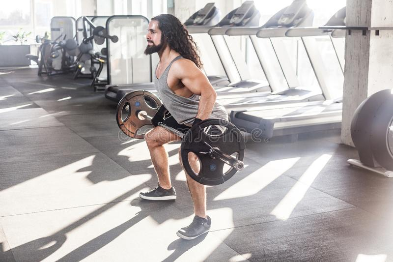 年轻成人爱好健美者侧视图画象有长的卷发的是在单独健身房的锻炼,prepearing对举的杠铃,做 库存照片