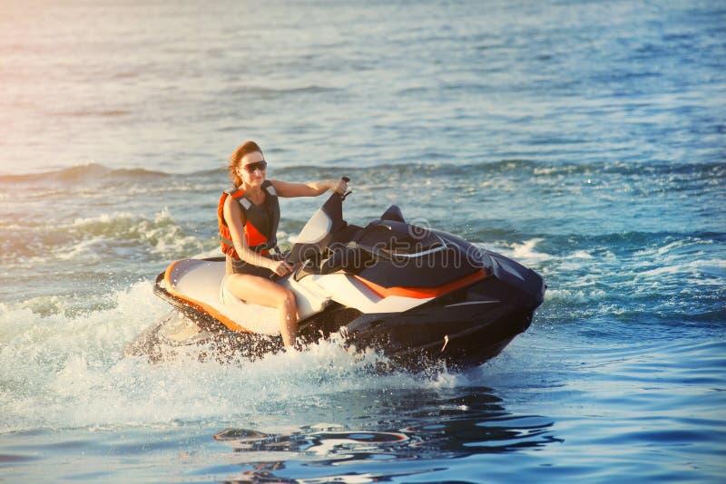 年轻成人运动的白种人妇女骑马喷气机滑雪在温暖的平衡的日落的海蓝色水中 海滩极限运动活动和 图库摄影