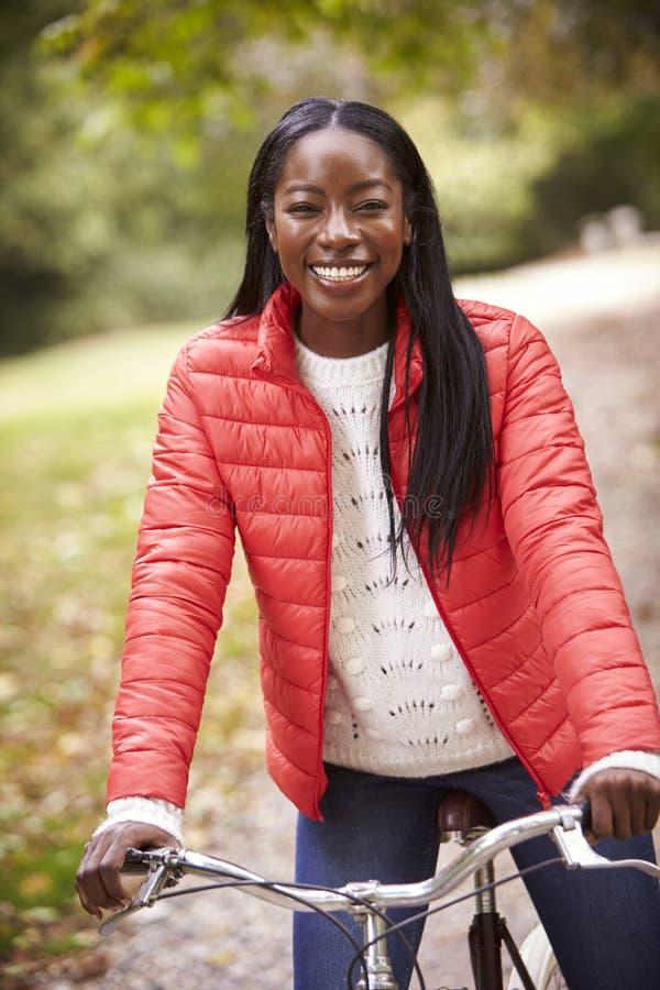 年轻成人黑人妇女坐葡萄酒自行车在微笑对照相机,正面图,关闭的公园  免版税库存图片