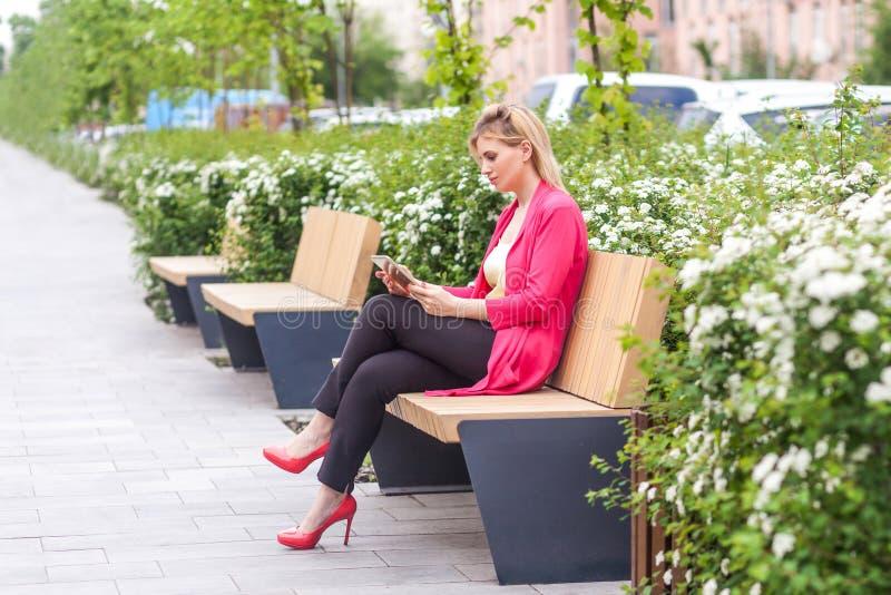 年轻成功的严肃的女实业家侧视图画象高雅样式的在长凳坐公园,拿着片剂和 免版税库存照片