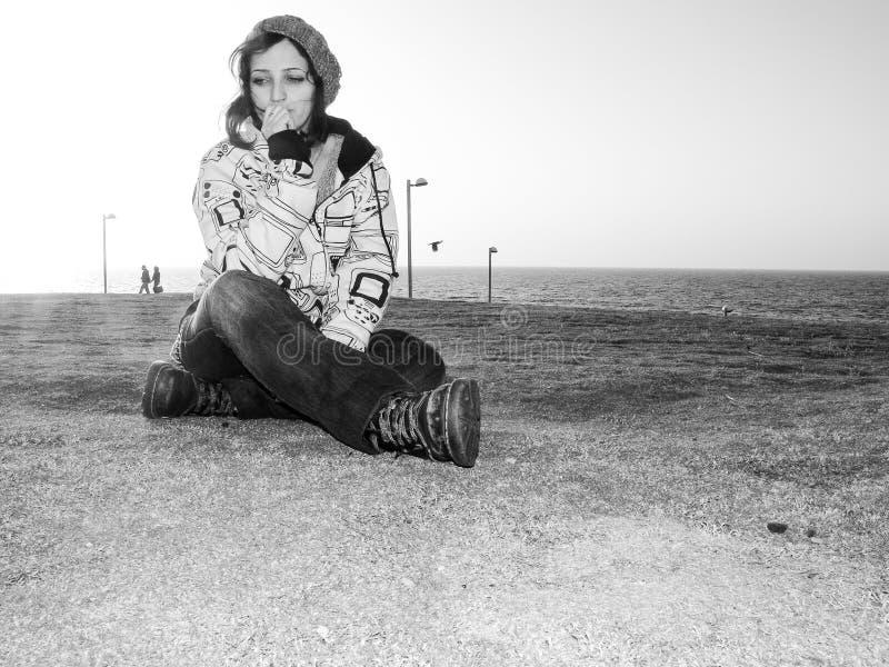 年轻成年女性、佩带的偶然服装、牛仔裤、帽子和有冠乌鸦,都市样式,坐草在一个公园有海景和 库存照片