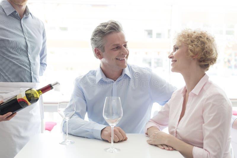年轻成熟夫妇的侍者服务的酒的中央部位在餐馆 免版税库存照片