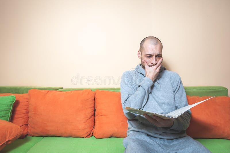 年轻或便服的中年病的人读医疗结果的在从他的医生的纸和意识到他有 库存照片