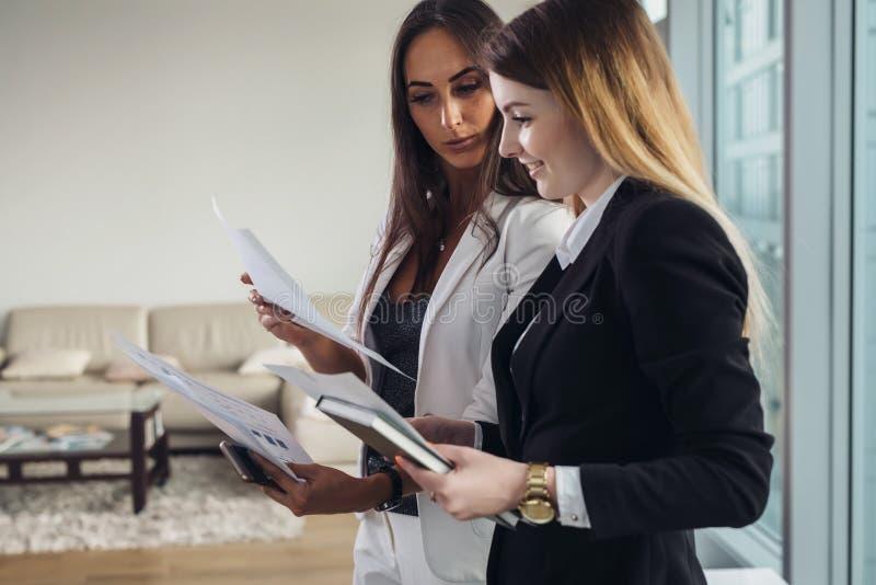 年轻房地产经纪商显示公寓和谈论合同和其他文件与顾客 免版税图库摄影