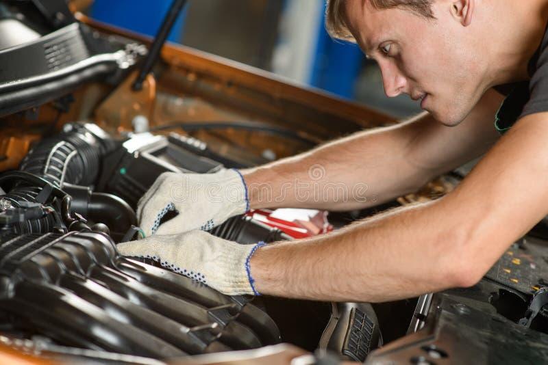 年轻技工修理发动机 免版税库存照片