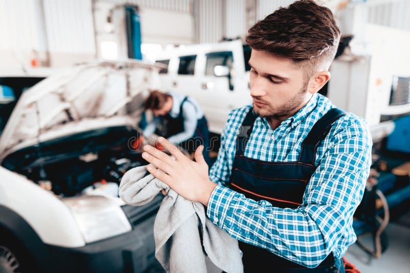 年轻技工抹手与在车库的毛巾 库存照片
