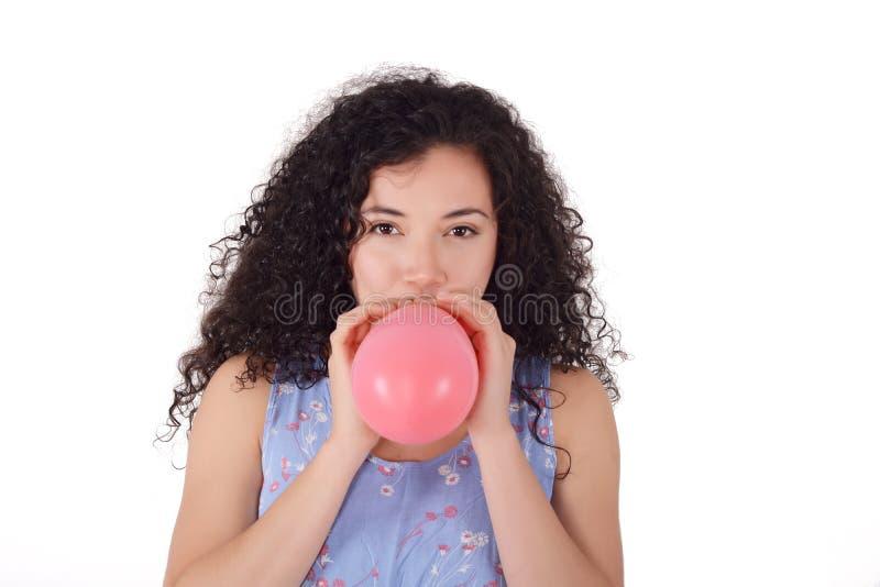 年轻拉丁妇女吹气球 图库摄影