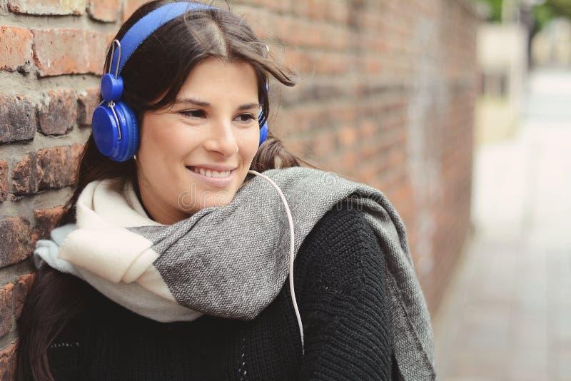 年轻拉丁妇女画象有蓝色耳机的 库存照片