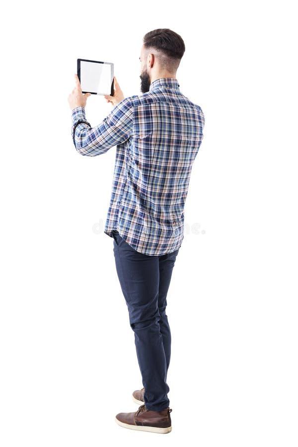 年轻拍照片的企业有胡子的人压料板片剂计算机边后面视图  免版税库存照片