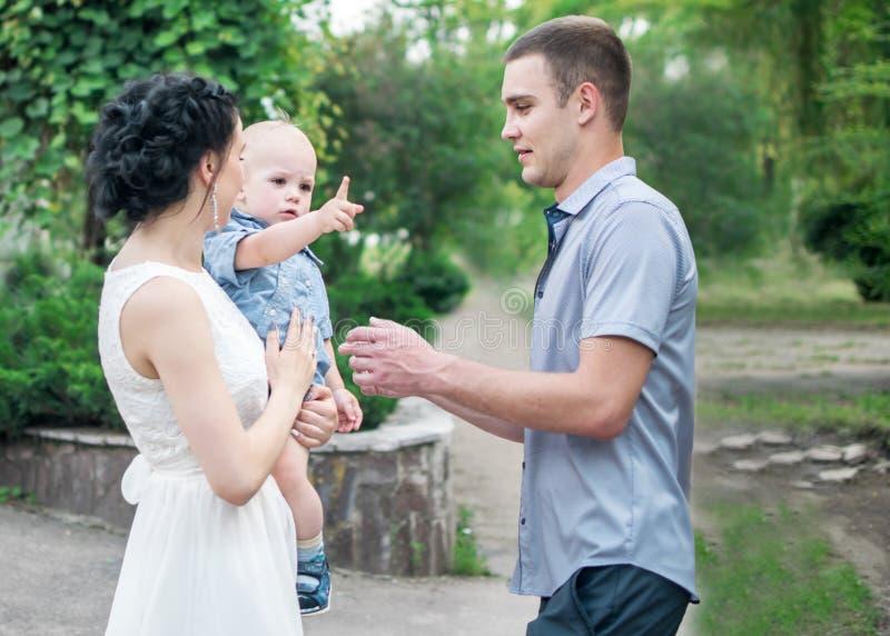 年轻拿着小儿子男婴的家庭俏丽的母亲画象和父亲在绿色夏天停放 他的pa婚礼的小男孩  免版税库存照片