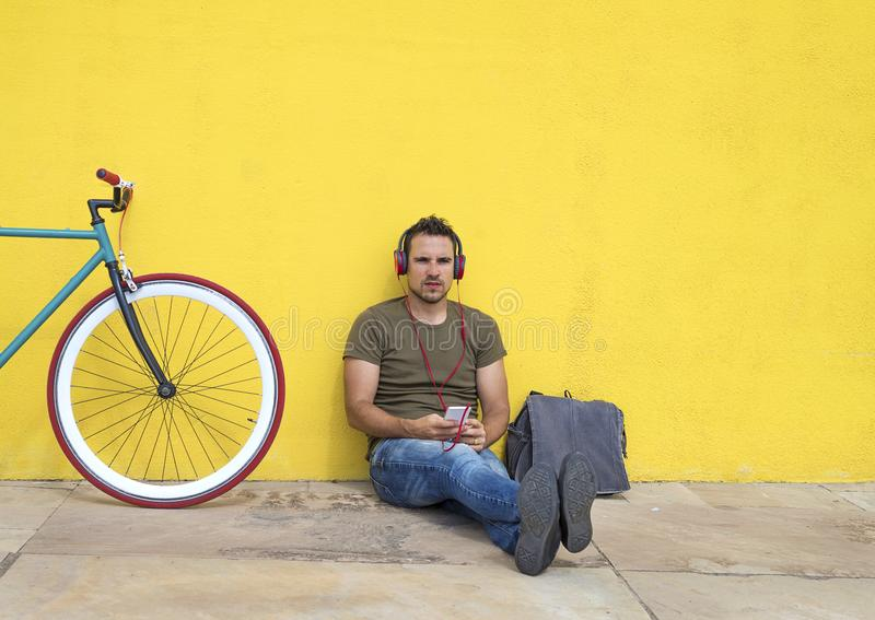 年轻放松在地板和听的音乐上的人佩带的太阳镜 坐对有他的计算机的黄色墙壁 图库摄影