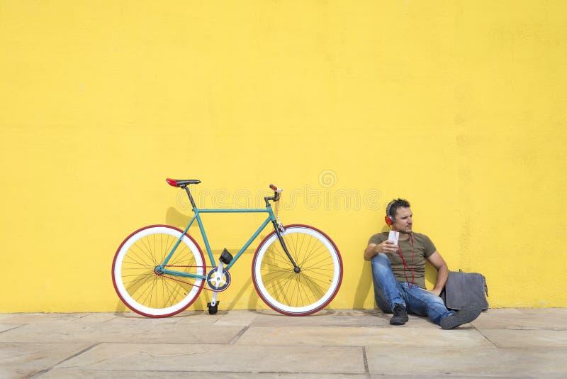 年轻放松在地板和听的音乐上的人佩带的太阳镜 坐对有他的计算机的黄色墙壁 库存照片