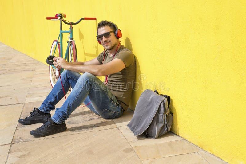 年轻放松在地板和听的音乐上的人佩带的太阳镜 坐对有他的计算机的黄色墙壁 免版税库存照片