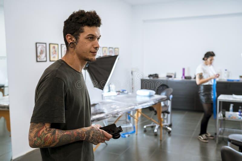 年轻文身的人在他的纹身花刺演播室 免版税图库摄影