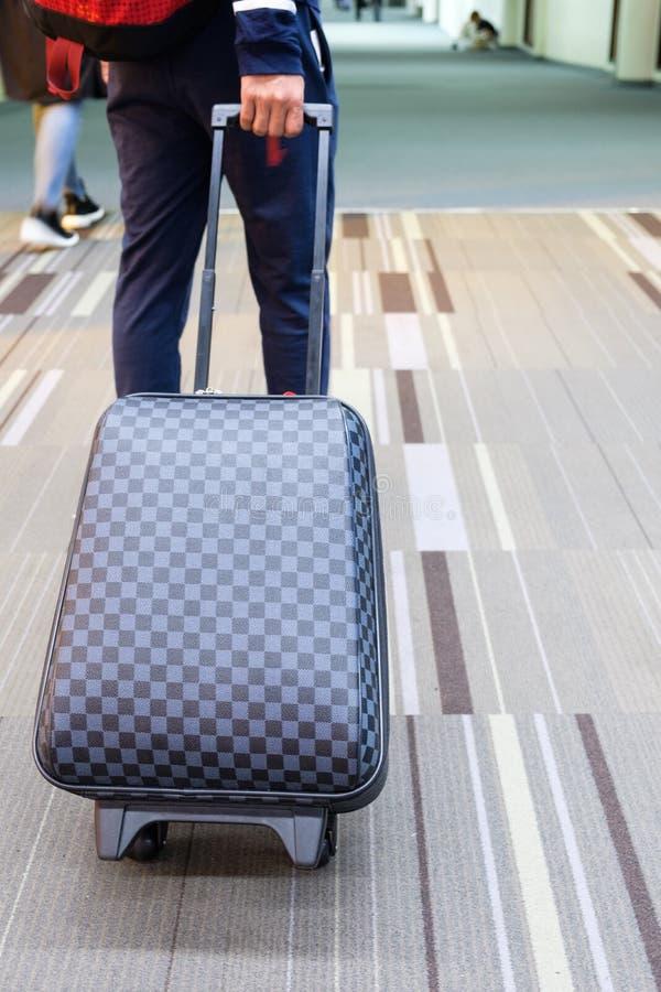 年轻旅客人扯拽的行李在机场 免版税库存图片