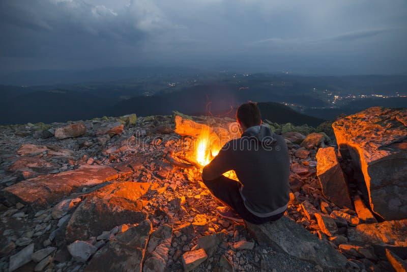 年轻旅游人坐夏夜在落矶山脉上面的明亮的火在多云天空下 库存照片