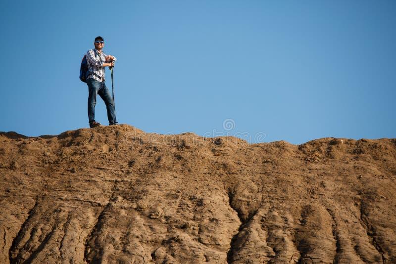 年轻旅游人照片用走的棍子在小山反对蓝天 免版税库存图片