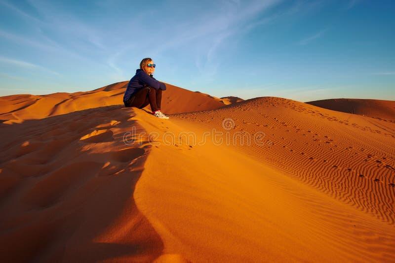 年轻旅游从沙漠沙丘的女孩观看的日出 免版税库存图片