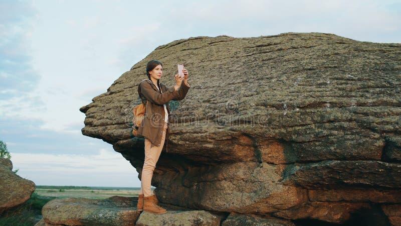年轻旅游在她的智能手机照相机的妇女背包徒步旅行者拍摄的风景在远足在日落的岩石以后 免版税库存图片