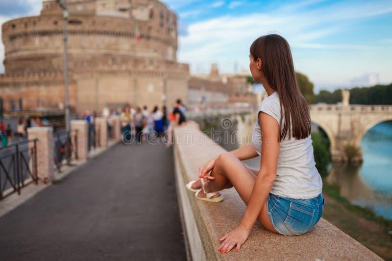 年轻旅游妇女坐古老堤防台伯河在罗马在日落 近天使桥梁和城堡  圣徒安吉洛 库存图片