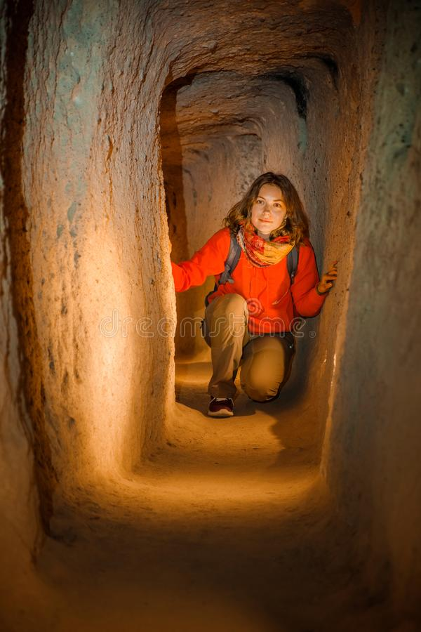年轻旅游妇女探索古老代林库尤地下洞城市 免版税库存照片
