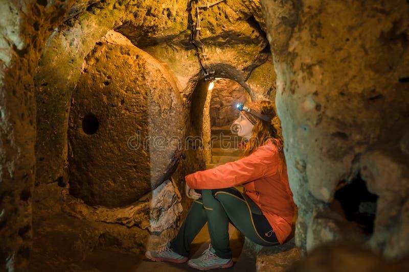 年轻旅游妇女探索古老代林库尤地下洞城市 免版税库存图片