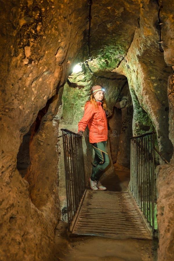 年轻旅游妇女探索古老Kaymakli地下洞城市 免版税库存照片