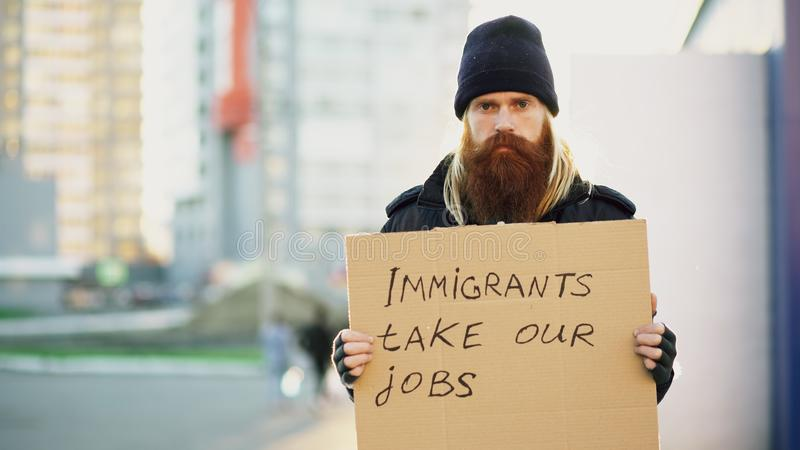 年轻无家可归的人画象有看照相机的纸板的和非常生气由于移民危机在欧洲 免版税图库摄影