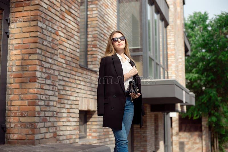 年轻时兴的女商人 在一件白色女衬衫和蓝色牛仔裤的时髦的女性模型 E 黑夹克是 图库摄影