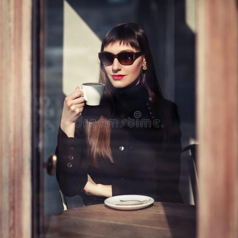 年轻时尚妇女在咖啡馆坐有杯子的街道热奶咖啡 在减速火箭的样式的户外画象 免版税库存照片