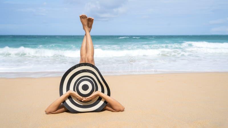 年轻时尚妇女在海滩放松 愉快的海岛生活方式 白色沙子、蓝色多云天空和热带海滩水晶海  库存图片